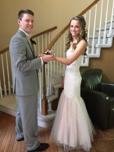 boy and girl in prom attire putting on the corsage