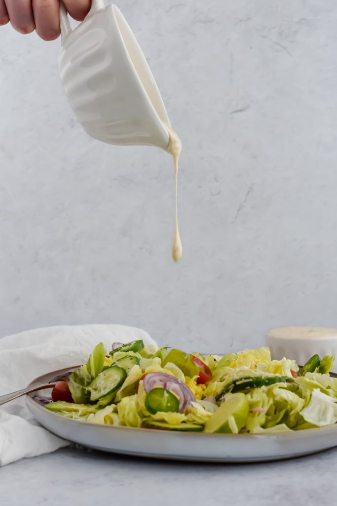 Pouring ranch dressing over Jalapeño Ranch Taco Salad