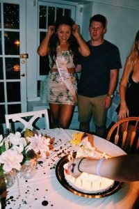 girl and guy standing in front of lit birthday cake