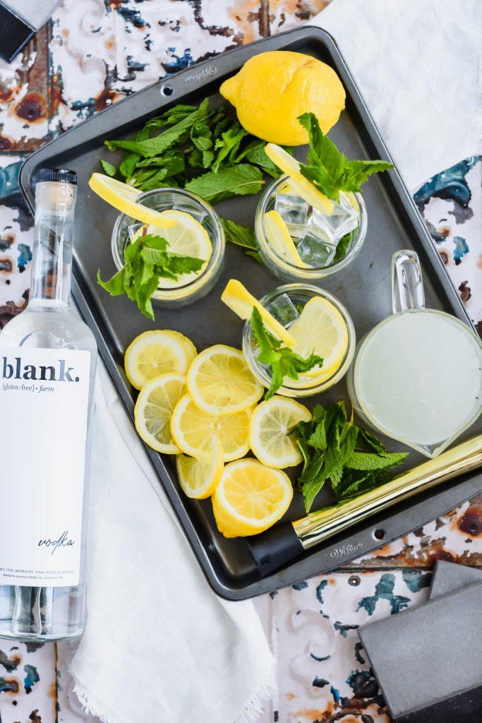 Skinny Lemonade Mojito ingredients on a sheet pan and a bottle of white rum