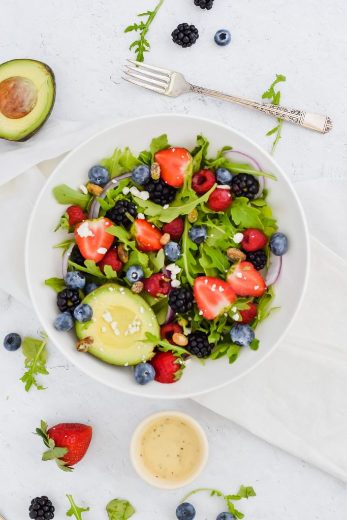 Salad bowl filled with arugula, berries, nuts, and avocado
