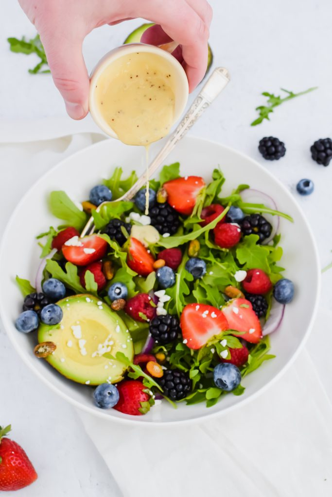 Pouring pale yellow dressing over a salad with berries, nuts and avocado