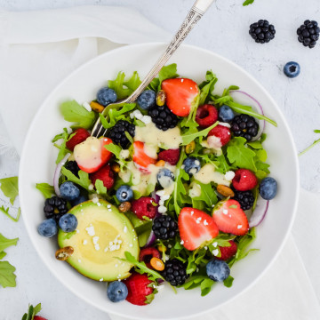 Salad in a white bowl with berries, nuts, avocado, and pale yellow dressing