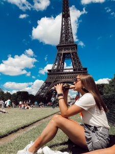 girl eating baguette in front of Eiffel Tower