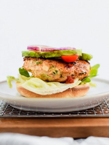 Avocado, red onion, cherry tomatoes, and lettuce on a Roasted Garlic and Basil Chicken Burger