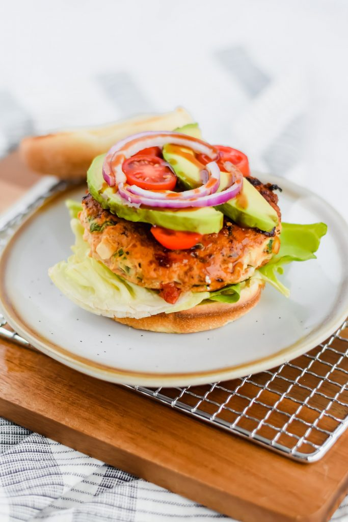 assembled chicken burger topped with avocado, tomato, and red onion and a toasted bun