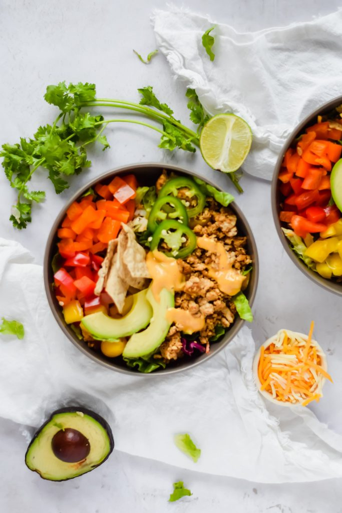 overhead shot of a nacho taco salad bowl surrounded by cilantro, lime, cheese, and avocado