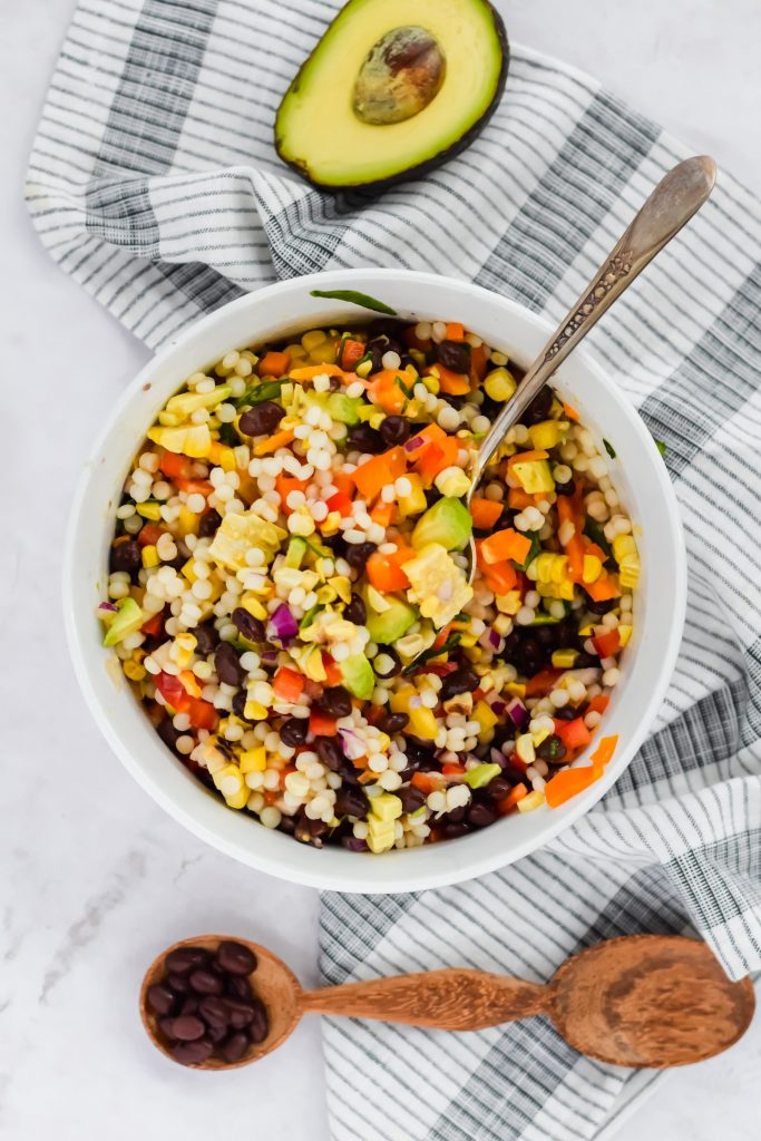 tossed couscous salad inside white ceramic bowl with avocado and black beans on the side
