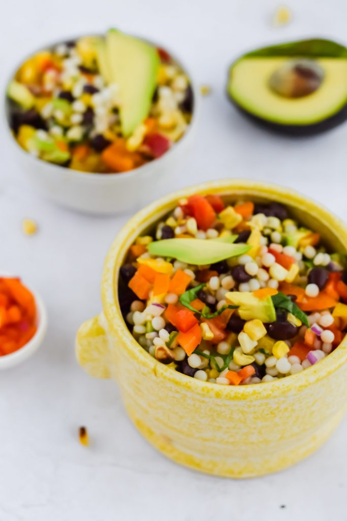 couscous salad chopped up in yellow ceramic bowl and topped with avocado