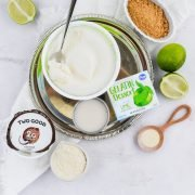 Ingredients for Key Lime Pie Milkshake including yogurt, Cool Whip, lime gelatin, fresh lime, almond milk, xantham gum, and crumbled graham cracker
