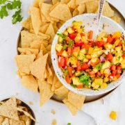 ceramic bowl filled with fresh mango salsa and chips with greenery around it