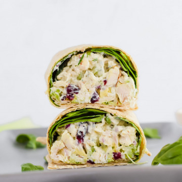 sliced wrap stacked on top of each other, filled with chicken salad and spinach on concrete plate