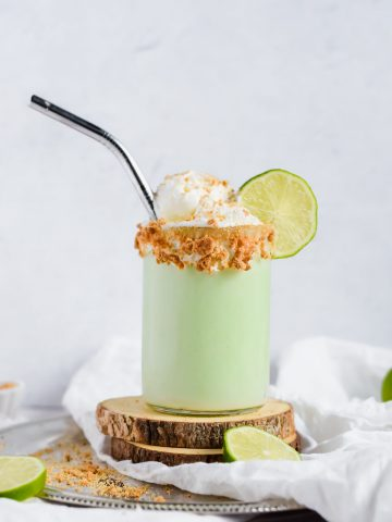 Key Lime Pie Milkshake topped with Cool Whip, crumbled graham cracker and a slice of lime with a metal straw