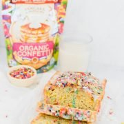 sliced funfetti pancake bread in loaf with glass of milk, sprinkles, and packaging behind