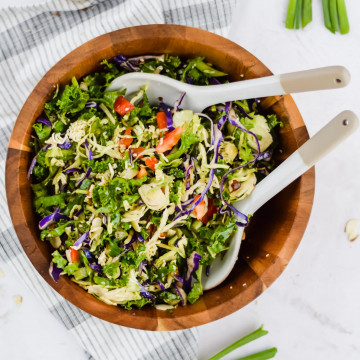 tossed cabbage slaw salad with tongs in wooded bowl with veggies surrounding it
