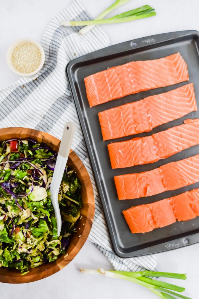 five pieces of salmon sliced on baking sheet with chopped salad on the side
