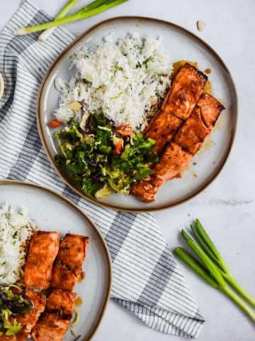 grilled salmon plated with teriyaki sauce, white rice and fresh salad