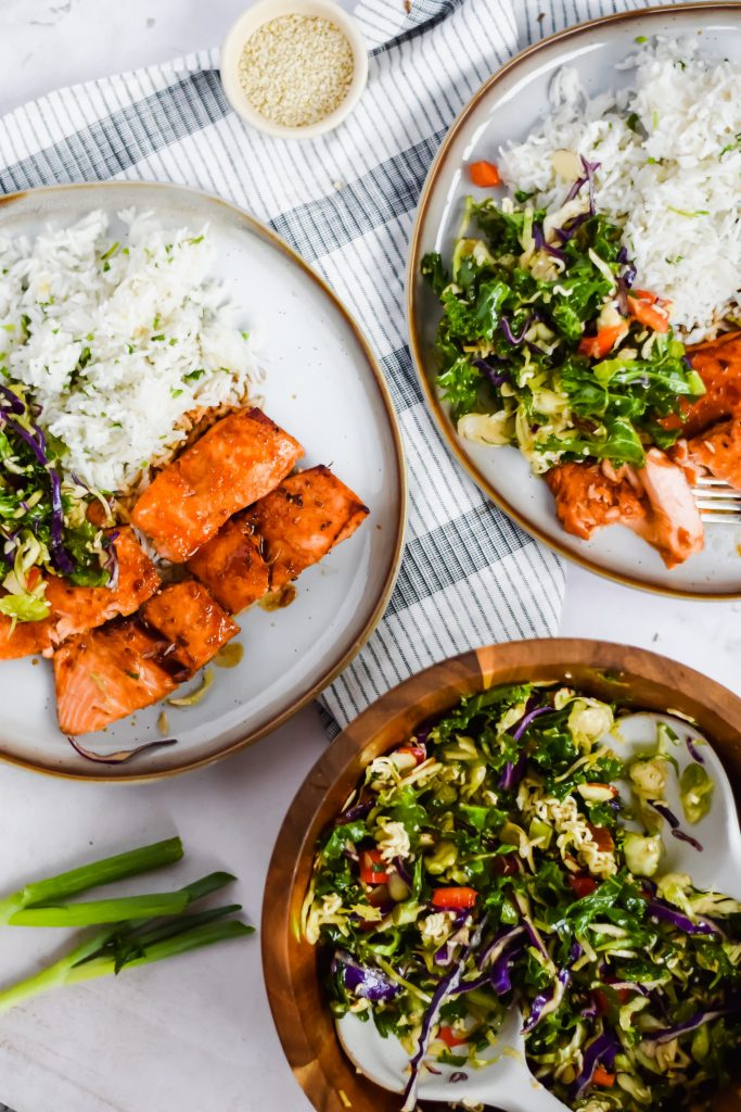 two full plates of cooked salmon, rice, and chopped salad on table