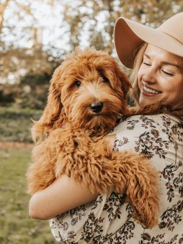 girl in sundress and sunhat holding her puppy, smiling at her