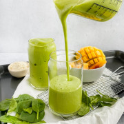 green smoothie being poured into glass cup