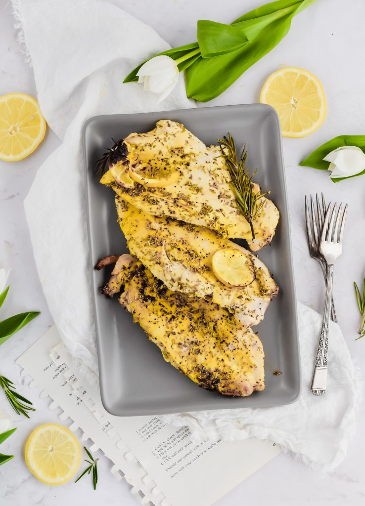 three chicken breasts grilled on grey plate and white background
