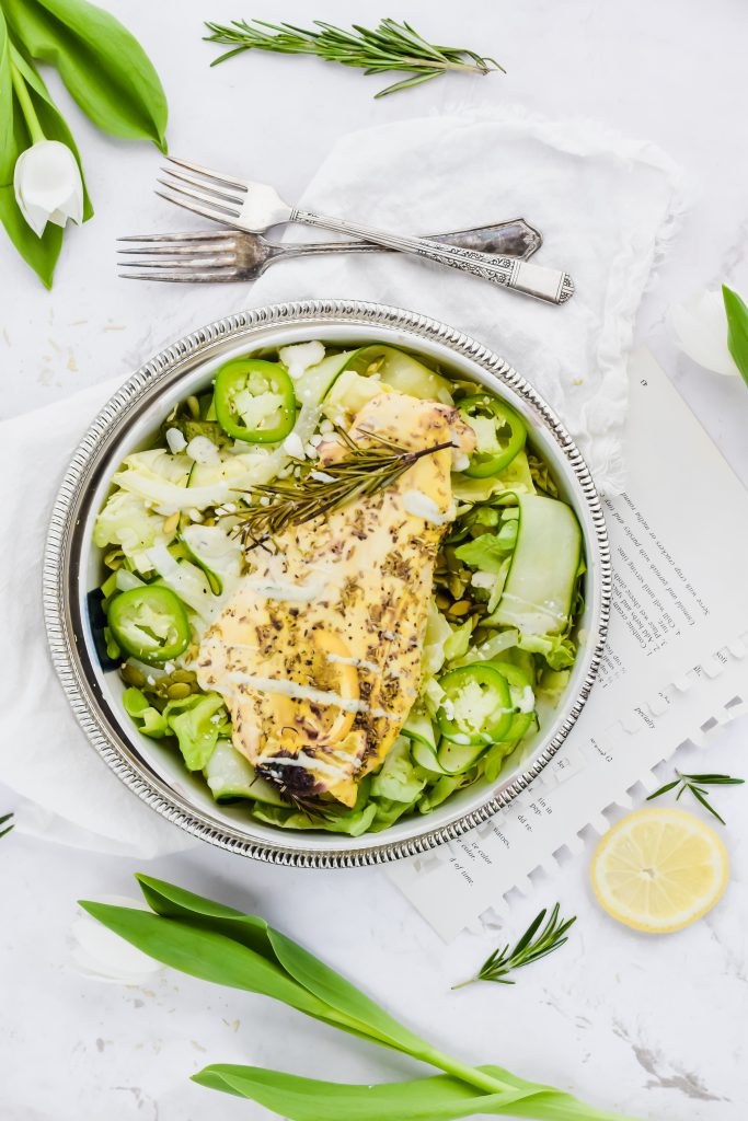 large dressed salad with lemon pepper chicken breasts on bed of greens with a fork and lemon surrounding it