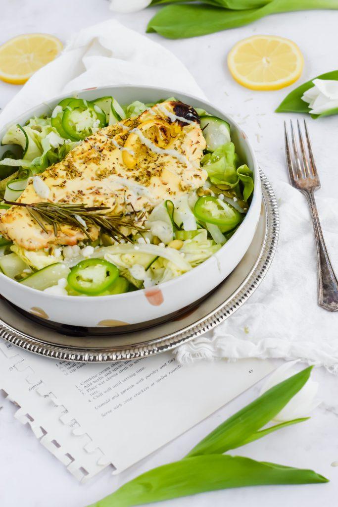 vibrant green goddess salad in white bowl on silver framed plate, white tulip surround and lemon slices
