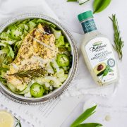 overhead shot of a large salad bowl with rosemary lemon pepper chicken and avocado green goddess dressing
