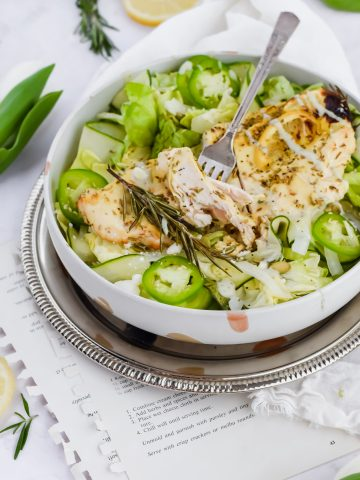 large salad bowl with plentiful amount of greens, lemon pepper grilled chicken and a fork piercing through one bite