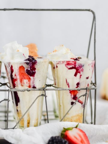 close up of milkshakes filled in glass jars, topped with whip cream and stacked with berries