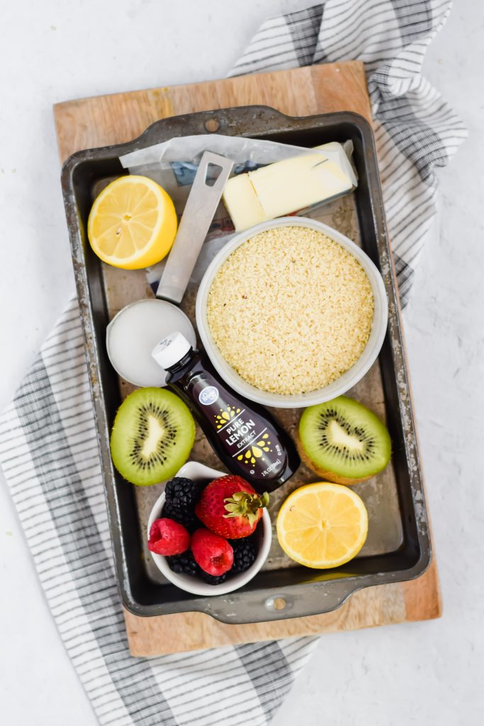 overhead image of ingredient shot: metal pan holding fruit, almond flour, lemon extract, and butter