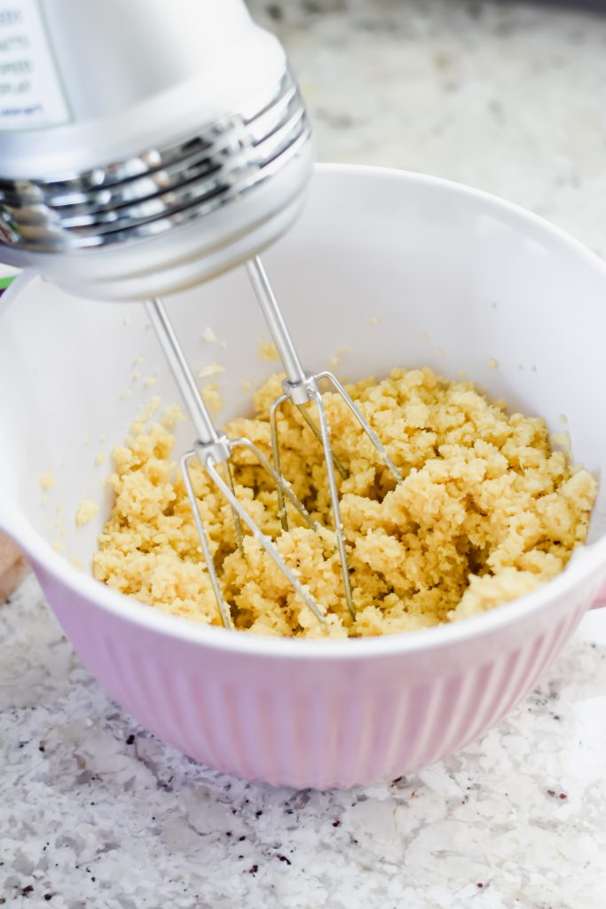 hand mixer in a pink bowl with crumbly texture of shortbread dough