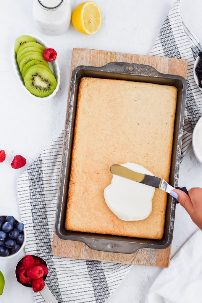hand holding a spatula, spreading the frosting