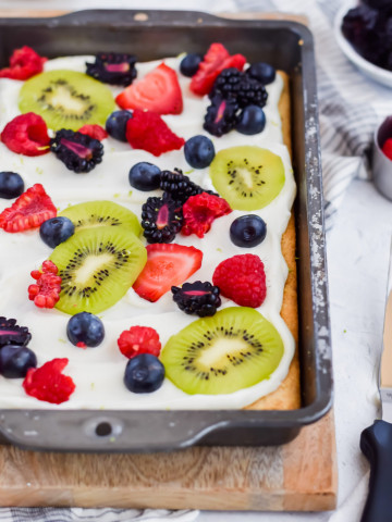 baked fruit pizza topped with frosting and fruit