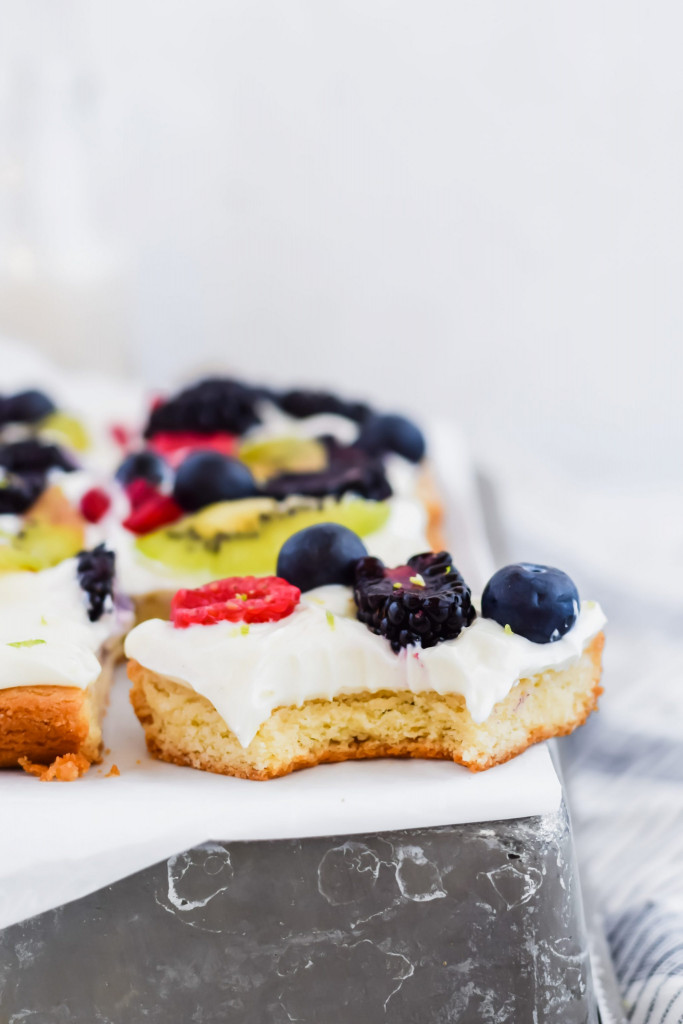 bite shot of fruit pizza on metal sheet pan and white background