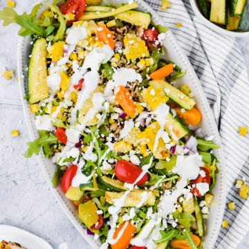 overhead image of salad fully assembled with dressing drizzled all around it