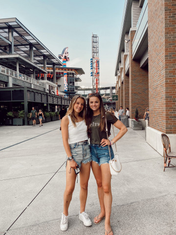 two girls standing in front of baseball stadium entrance