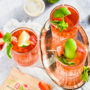 filled cocktail glasses with Caribbean Rum Punch topped with fresh mint, strawberries, and lime