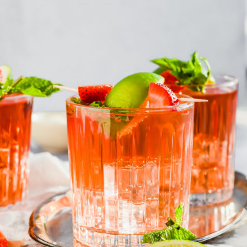 close up filled cocktail glasses with Caribbean Rum Punch topped with fresh mint, strawberries, and lime