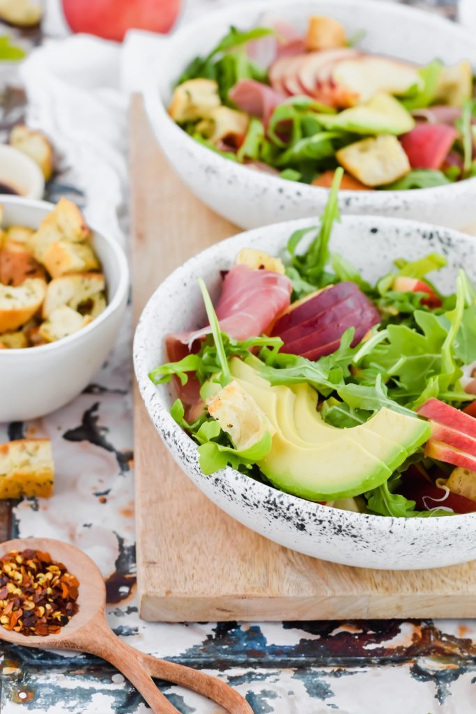 focus image of sliced avocado on salad with prosciutto and arugula