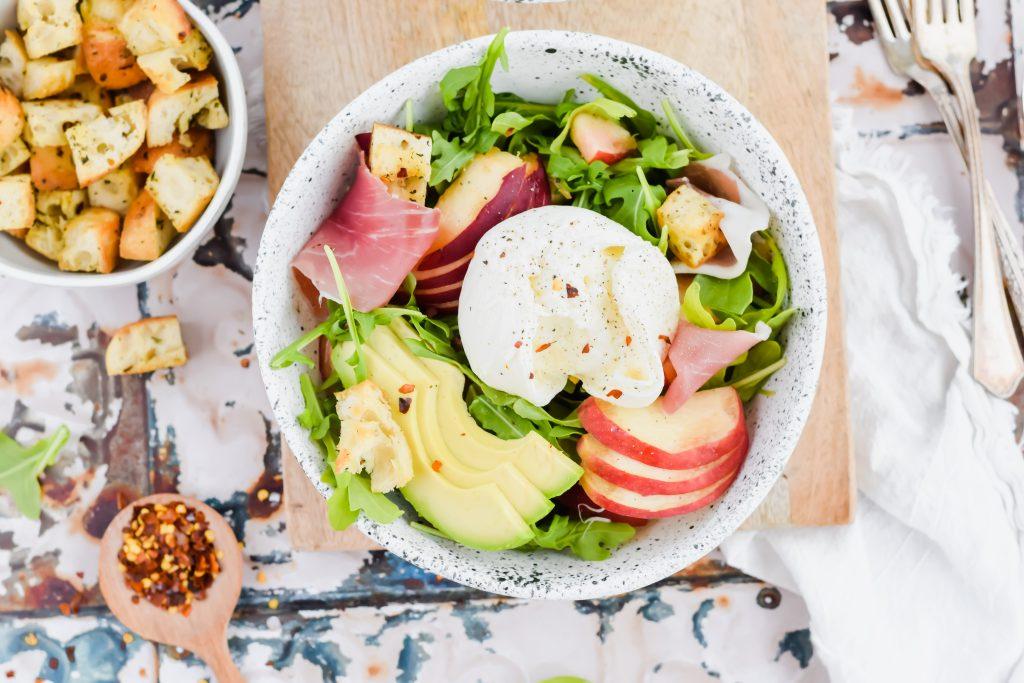 overhead image of peach burrata arugula salad in white ceramic bowl on antique tile backdrop