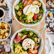 two filled white salad bowls with all ingredients chopped and fully dressed on antique metal tile backdrop