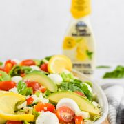 close up image of vibrant caprese salad with avocado, sliced lemons, and arugula salad on white ceramic dish framed on wooden cutting board with dressing bottle in background