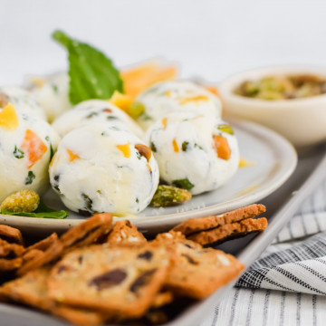 90 degree image of dried mango goat cheese balls on a platter with mint and crackers garnished around it