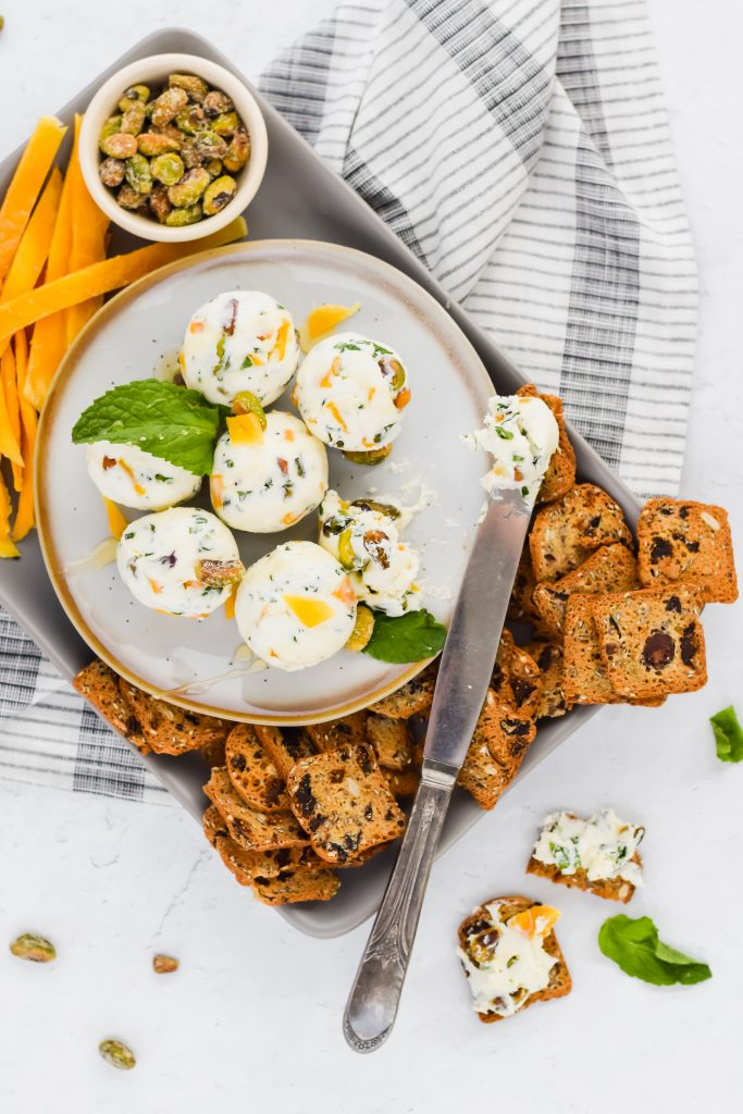 butter knife spreading dried mango mint goat cheese balls on platter with crackers around it