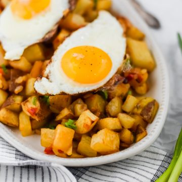 fried egg on top of breakfast potato hash with ketchup and vegetables in the background