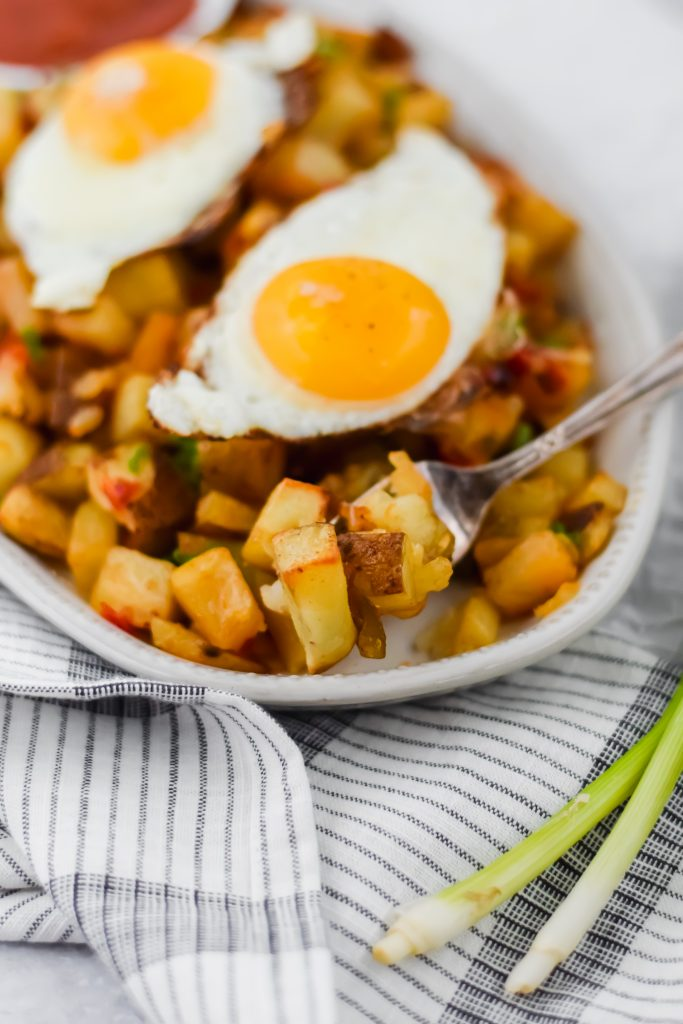 fork piercing roasted potatoes with fried egg on top