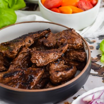 juicy, perfectly beef tips covered in sauce in a black bowl on antique tile backdrop