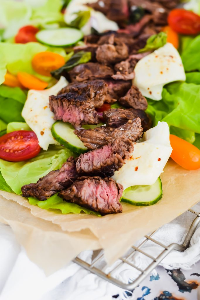 close up of seared beef tips sliced and placed on top of bed of lettuce and vegetables