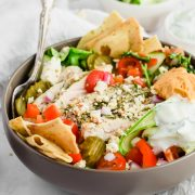 45 degree close up image of loaded salad bowl with sliced grilled chicken, pita chips, tomatoes, red onions, pickles, dollop of hummus, tabbouleh, and tzatziki dressing